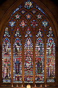 Stained glass window in the main chapel at St Etheldreda's Church in London, England, United Kingdom. St Etheldreda's Church was the town chapel of the Bishops of Ely from about 1250 to 1570. It is the oldest Catholic church in England and one of only two remaining buildings in London from the reign of Edward I. It was once one of the most influential places in London with a palace of vast grounds. It was like an independent state, the Bishop of Ely's place in London or Ely Place as it is now called, and its chapel took its name from one of England's most popular saints of the day, Etheldreda.