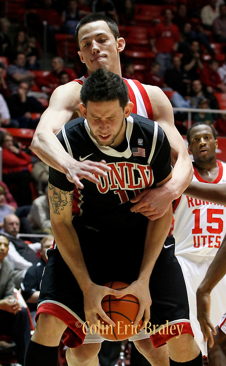 UNLV forward Carlos Lopez, front, is fouled by Utah center Jason Washburn during the second half of an NCAA college basketball game in Salt Lake City, Utah, Saturday, March. 5, 2011. UNLV defeated Utah 78-58. (AP Photo/Colin E Braley)