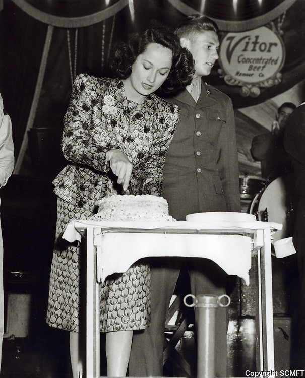 1944 Merle Obregon cuts birthday cake at the Hollywood Canteen