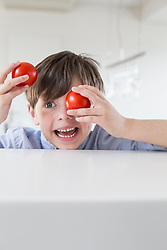 Boy making faces with tomatoes