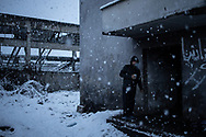 Man from Afghanistan is seen eating a noodles soup, provided by some volunteers outside his makeshift shelter in an abandoned factory.  A migrant from Afghanistan having some warm soup ouside his makeshift shelter during an heavy snowfall. Dozens migrants and refugees are living in a makeshift camp in an abandoned factory in the town of Bihac. January 25, 2021. Federico Scoppa