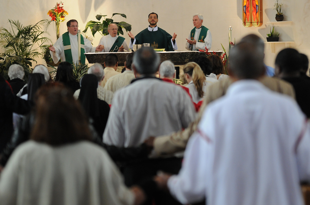 Father Carmelo Mendez leads his parishioners in the Lord's Prayer at St. Eulalia Catholic Church in Maywood.