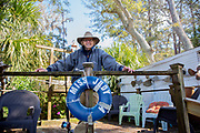 Senior adult fisherman business owner stands on pier.