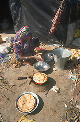 Woman in shanty town cooking chapattis over open fire,