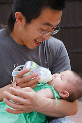 Chinese father feeding his baby daughter