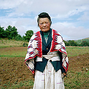 """Portrait of an elderly Big Flowery Miao woman wearing a traditional handwoven hemp skirt and woollen, handwoven cloak. Qie Chong village, Guizhou Province, China. Although hemp production is decreasing because land is needed for cash crops and manufactured cotton is readily available, it is still grown, spliced and women in remote mountain villages in Guizhou Province. Almost 35% of Guizhou's population is made up of over 18 different ethnic minorities including the Miao. Each Miao group became isolated in these mountainous regions, hence the present day diversity in their culture, costume and dialects. According to a popular saying, """"if you meet 100 Miaos, you will see 100 costumes."""""""