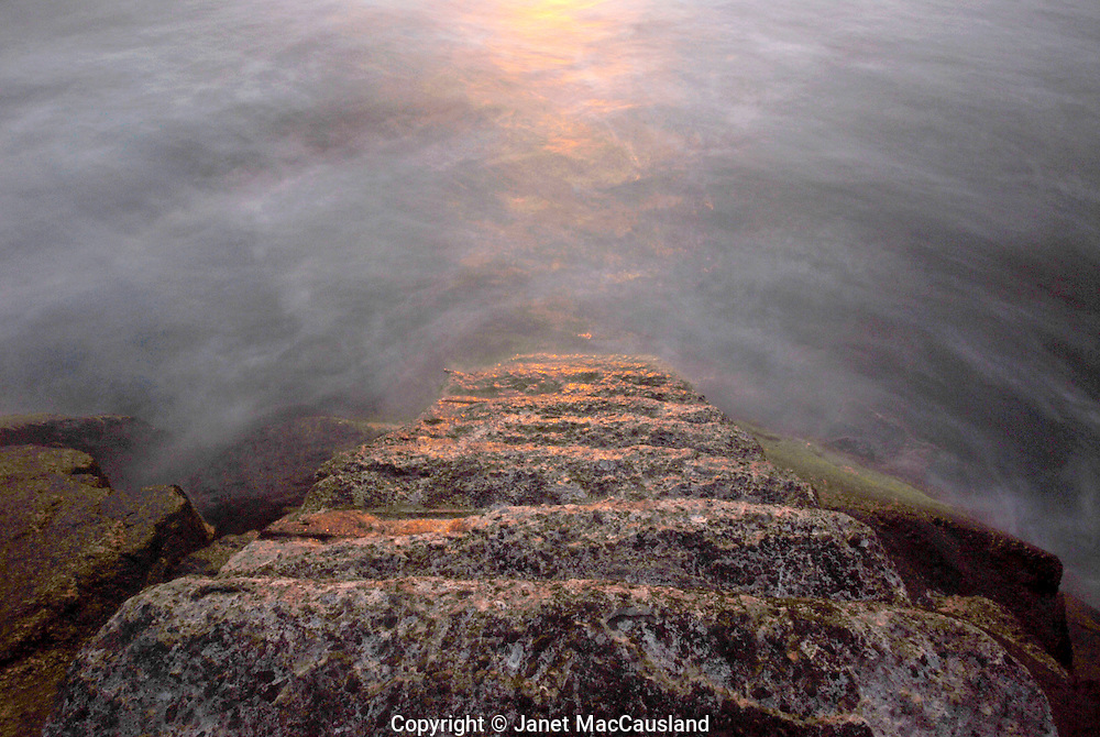 This is a stairway from a Newport, Rhode Island jetty to the ocean, and a reflection of the sun. I know of another such stairway in Truro, Massachusetts. I do not know why they have been built.