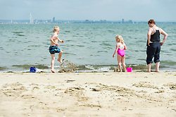 © Licensed to London News Pictures. 14/06/2014. Ryde, Isle of Wight, UK. A family plays on the beach on a hot sunny morning.  The UK is experiencing a period of hot sunny weather with temperatures over the weekend expected to reach 74 F (23 C).  Photo credit : Richard Isaac/LNP