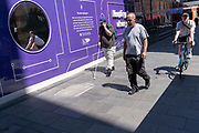 Pedestrians walk and a cyclist pedals past a purple hoarding that screens off refurburshment works in the West Ends Leicester Square, on 16th July 2021, in London, England.