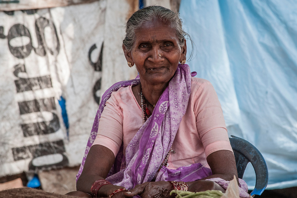 An Indian woman sells vegetables along the road outside of Goa, India