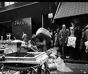 Moore Street, Dublin.      (J97)..1975..23.12.1975..12.23.1975..23rd December 1975..For well over a hundred years Moore Street has served the citizens of Dublin. The longest running open air fruit and vegatable market offers value for money,particularly to those where money is in short supply. Predominately a fruit and veg market there are several traders who sell fish and seasonal goods, as illustrated by the photographs showing turkeys and holly wreaths being sold on the run up to Christmas..This image shows a youngster starting to stock up that most important of modes of transport, The pram.