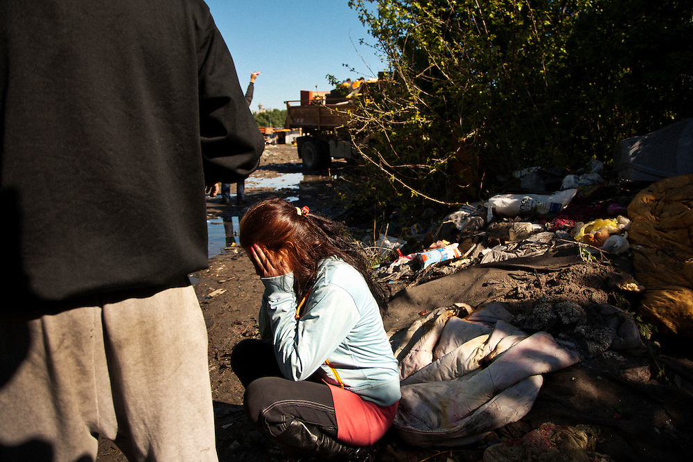 Woman crying as her family's belongings are packed by city workers. The Belville camp in New Belgrade on the morning of its destruction by the Belgrade city government.