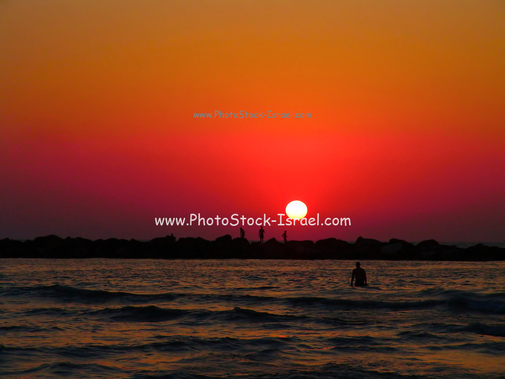 Silheoutte of fishermen and a surfer on a breakwater at sunset