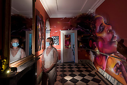 """© Licensed to London News Pictures. 22/07/2020. LONDON, UK. A staff member views works by Mr Cenz. Preview of """"disCONNECT"""", a new exhibition transforming a Victorian townhouse in Clapham Common, south west London displaying works by ten urban UK based as well as international artists.  The show is presented by Schoeni Projects, a new contemporary arts platform based in London and Hong Kong, and is accessible online and by appointment 24 July – 24 August 2020.  Photo credit: Stephen Chung/LNP"""