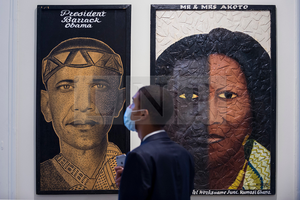 """© Licensed to London News Pictures. 08/10/2020. LONDON, UK. A staff member views """"President Barack Obama"""", c 2019, by Almighty God (Kwame Akoto).  Preview of 1-54 Contemporary African Art Fair, the leading international art fair dedicated to contemporary art from Africa and its diaspora, taking place at Somerset House.  The fair showcases the work of more than 110 emerging and established artists from Africa and is the only physical art fair taking place during Frieze Week.  Photo credit: Stephen Chung/LNP"""