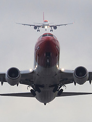 © Licensed to London News Pictures. 21/12/2018. Gatwick, UK. An aircraft takes off from Gatwick as another (top) approaches for landing, as flights resume. Further delays are expected today after two days of disruption due to multiple sightings of drones over the airfield. Thousands of passengers have been stranded as flights have been cancelled or diverted. Police are still hunting the drone operator. Photo credit: Peter Macdiarmid/LNP