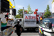 """A parade van with an """"AIDS is not over"""" banner on it at Tokyo Rainbow Pride festival, Yoyogi Park, Tokyo, Japan. Sunday April 27th 2014 This was the third year this annual gay-pride event has been held in Japan capital.with food, fashion and health care stalls and musical performances set up in Yoyogi Park event square and a colourful parade around Shibuya at 1pm."""
