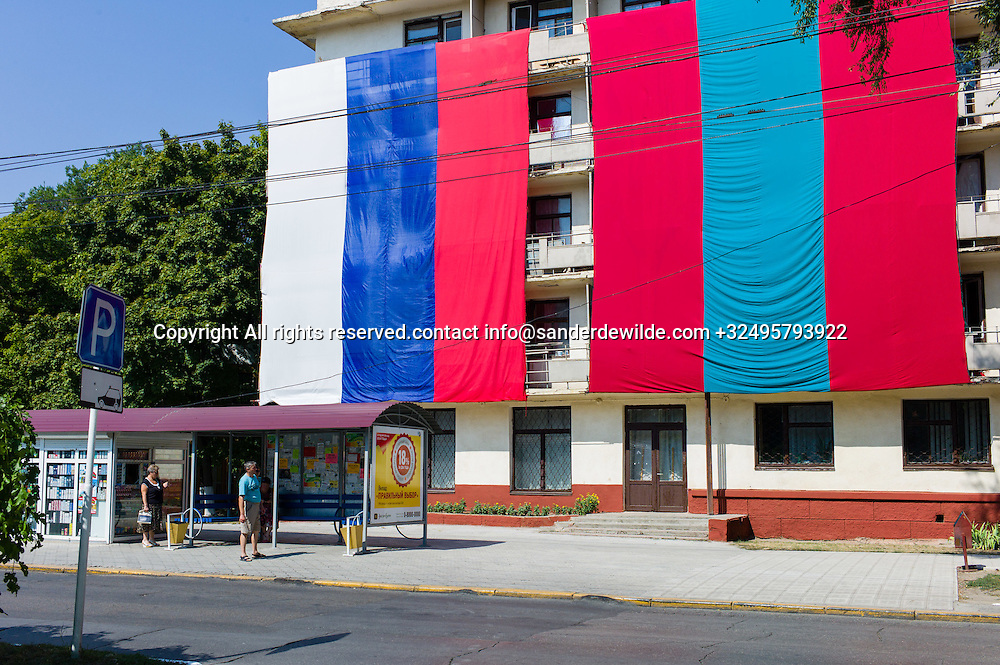 20150829  Moldova, Transnistria,Pridnestrovian Moldavian Republic (PMR) Tiraspol. A couple walks by  an appartmentbuilding that is being decorated with giant Transnistrian and Russian banners brotherly next to each other.All for the 25th birthday of the 'country'