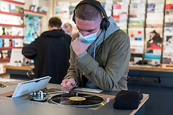© Licensed to London News Pictures. 29/08/2020. LONDON, UK. A customer wearing a facemask listens to music in Phonica Records. Analogue music fans visit independent record shops in Soho to celebrate vinyl music on the rescheduled 13th Record Store Day, originally planned for April, but postponed due to the coronavirus pandemic.  Over 200 independent record shops across the UK come together annually to celebrate the unique culture of analogue music with special vinyl releases made exclusively for the day.  Sales of vinyl have risen, with 4.3m records sold in the UK during 2019, more than a 12-fold increase on the levels seen in 2011. Photo credit: Stephen Chung/LNP