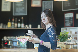 Young waitress serving coffee and croissant in coffee shop, Freiburg Im Breisgau, Baden-Wuerttemberg, Germany