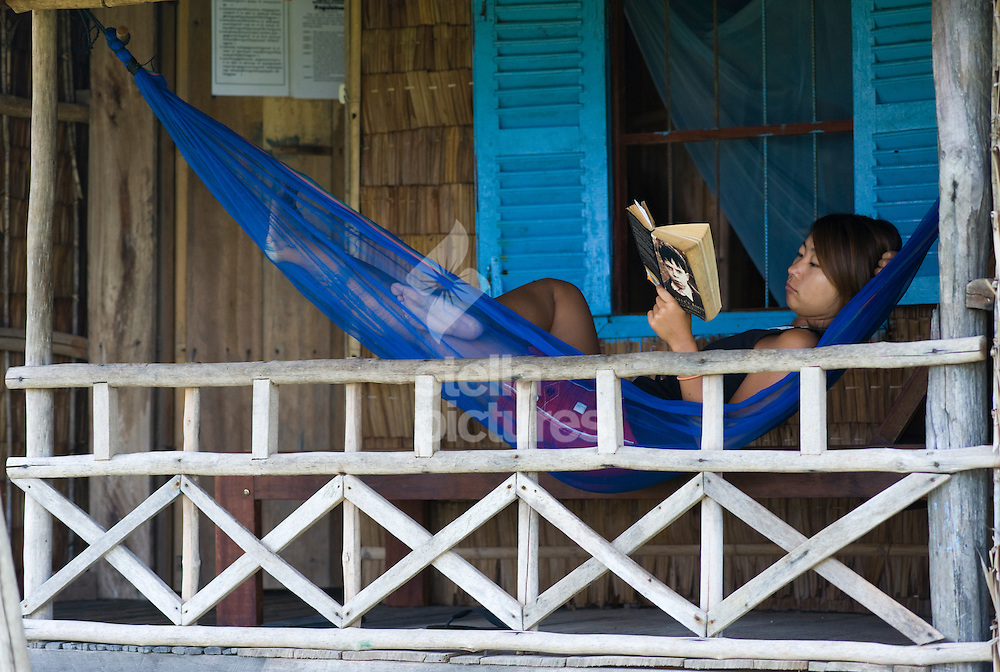Picture by Daniel Hambury. .7/3/11..A tourist takes a break to read her book in a hammock on Rabbit Island, Cambodia.