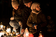 A father with two daughters light a candle in front of the monument to the Polish victims of communism at Rakowicki Cemetery in Krakow, Poland 2019.