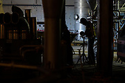 A construction worker cuts a piece of piping in an air exchange area at the Puris pea protein processing facility in Dawson, Minnesota, on Tuesday, June 8, 2021.