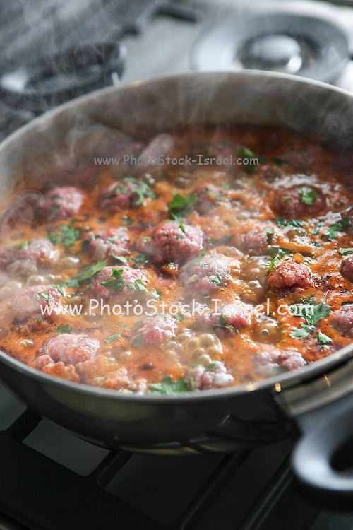 Cooking Moroccan meatballs in tomato sauce Meatballs cook in a pot