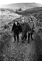 Man with learning difficulties walking with carers in countryside,