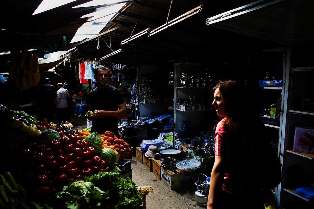 A fruit seller and a customer at the Prishtina market. Kosovo.