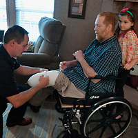 Molly Spearman, 7, stands on her fathers wheel chair while Tom Spearman helps his father, Lee, with his with his prosthetic legs at their home in Ingold, N.C., Sunday, March 16, 2014. Lee Spearman was hospitalized in December of 2013 with an infection that was ravaging his body and almost took his life and resulted in having both of his legs amputated below the knee and all the fingers on his left hand. Photo By Mike Spencer/StarNews Media