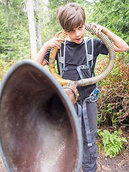 Girl listening to the sounds of the woods with big ear trumpet in black forest, Feldberg, Baden-Württemberg, Germany