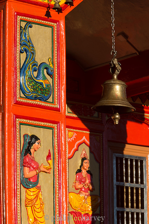 Jakhoo Temple entrance with reliefs and brass bell hanging, Shimla, India