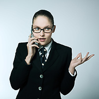 studio shot portrait of a beautiful young woman in a costume suit calling by phone
