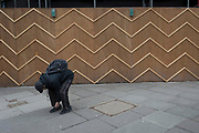 A man bends down to adjust his trousers next to the zigzag battens of a construction hoarding at Notting Hill, on 13th March 2018, in London, England.