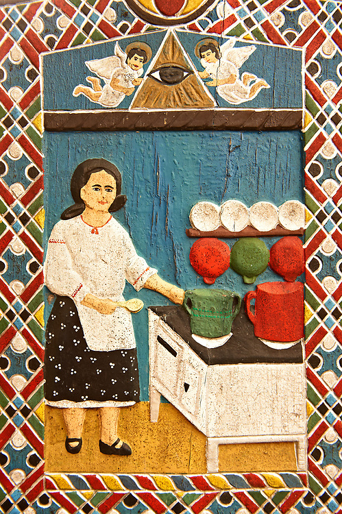 Tombstone of a house wife, The  Merry Cemetery ( Cimitirul Vesel ),  Săpânţa, Maramares, Northern Transylvania, Romania.  The naive folk art style of the tombstones created by woodcarver  Stan Ioan Pătraş (1909 - 1977) who created in his lifetime over 700 colourfully painted wooden tombstones with small relief portrait carvings of the deceased or with scenes depicting them at work or play or surprisingly showing the violent accident that killed them. Each tombstone has an inscription about the person, sometimes a light hearted  limerick in Romanian. .<br /> <br /> Visit our ROMANIA HISTORIC PLACXES PHOTO COLLECTIONS for more photos to download or buy as wall art prints https://funkystock.photoshelter.com/gallery-collection/Pictures-Images-of-Romania-Photos-of-Romanian-Historic-Landmark-Sites/C00001TITiQwAdS8