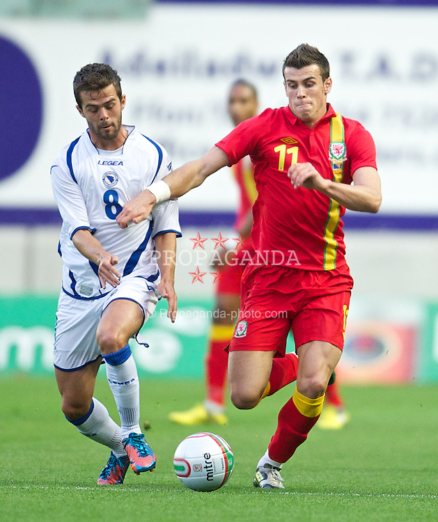 LLANELLI, WALES - Wednesday, August 15, 2012: Wales' Gareth Bale in action against Bosnia-Herzegovina's Miralem Pjanic during the international friendly match at Parc y Scarlets. (Pic by David Rawcliffe/Propaganda)