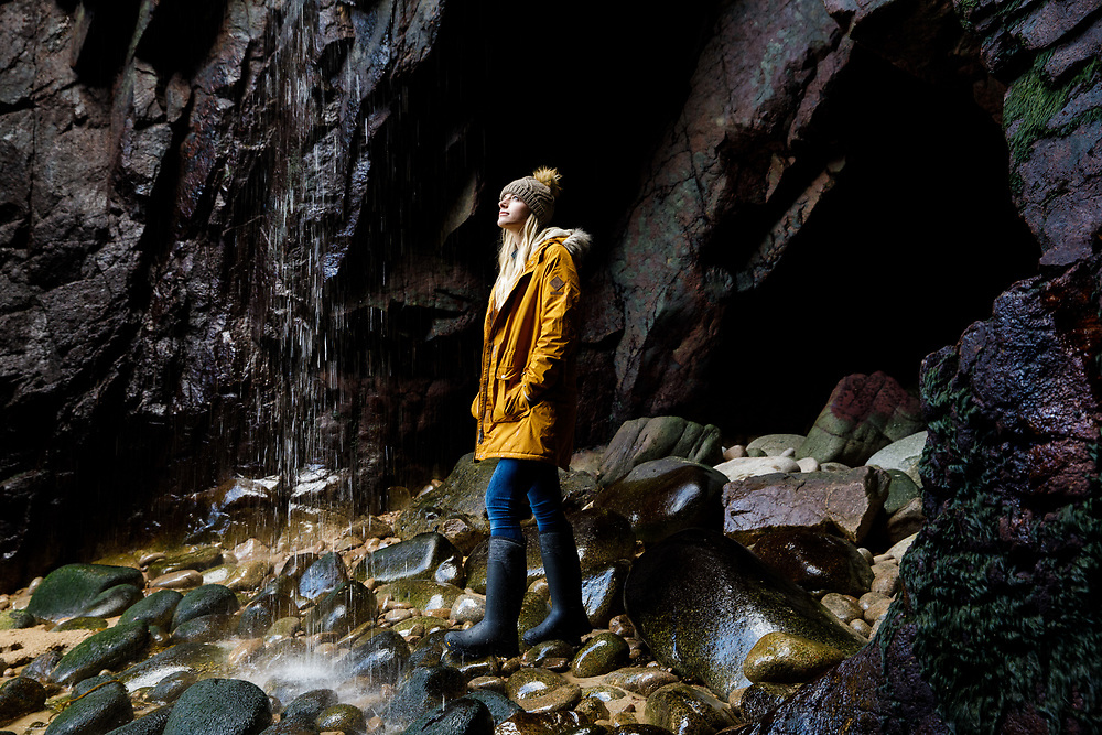 Woman looking up at the waterfall in a cave at Plemont beach, a popular bay with tourists in Jersey, CI