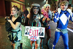"© Licensed to London News Pictures . 27/12/2018. Wigan, UK. A leave-supporting woman dressed up as "" Brexit "" , with photos of Jacob Rees-Mogg and Nigel Farage hanging from her neck . Revellers in Wigan enjoy Boxing Day drinks and clubbing in Wigan Wallgate . In recent years a tradition has been established in which people go out wearing fancy-dress costumes on Boxing Day night . Photo credit: Joel Goodman/LNP"