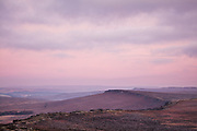 Soft dawn hues of pink and purple fill the skies over a frosty Stanage Edge, which can be seen snaking across the scene. Derwent Edge and Bleaklow can be seen on the horizon in this landscape scene of the Derbyshire Peak District, England, UK.