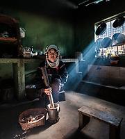 KYAING TONG, MYANMAR - CIRCA DECEMBER 2017: Portrait of an Akha woman in her kitchen at the Wan Pin Akha Village in Kyaing Tong.