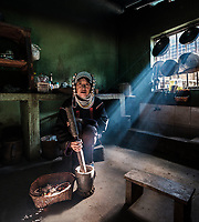 KYAING TONG, MYANMAR - CIRCA DECEMBER 2017: Portrait of an Akha woman in her kitchen at the Wan Pin Akha Village in Kyaing Tong.