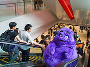 "27 MARCH 2015 - BANGKOK, THAILAND: People reach out to touch ""Grimace,"" a fast food character used to promote McDonald's restaurants in Thailand, in ""EmQuartier,"" a new mall in Bangkok. ""EmQuartier"" is across Sukhumvit Rd from Emporium. Both malls have the same corporate owner, The Mall Group, which reportedly spent 20Billion Thai Baht (about $600 million US) on the new mall and renovating the existing Emporium. EmQuartier and Emporium have about 450,000 square meters of retail, several hotels, numerous restaurants, movie theaters and the largest man made waterfall in Southeast Asia. EmQuartier celebrated its grand opening Friday, March 27.   PHOTO BY JACK KURTZ"