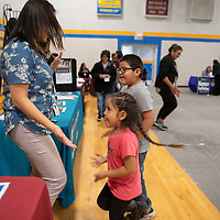 Naudaya Clyde, a fitness specialist at the Tséhootsooí Medical Center as part of the Nihi Dine'é Bá Wellness Center, dances with brother and sister Kohen Ashley, 6 and Kyraa Ashley, 5, Friday, Jan. 18 at the Winter Culture Festival at Valley High School in Sanders. Clyde checks their heart rates before and after dancing to compare and talks about the importance of exercise.