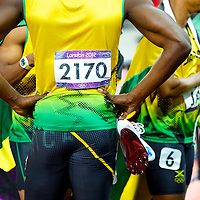 Usain Bolt holds his cleats as the Jamaican 4x100m relay team is interviewed by the media after winning gold and setting a new world record of 36.84 seconds during the 2012 London Summer Olympics.