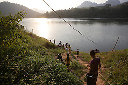 At the end of the day many of the villagers, young and old head down to the river to wash, collect water for the family and tend their river gardens. Had Mad, Pak Ou district Luang Prabang Province. Lao PDR