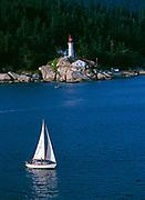 Sailboat and Atkinson Lighthouse at Point Atkinson, Lighthouse Park, Burrard Inlet, British Columbia, Canada.