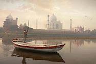 An Indian boat driver crosses the Yamuna River with the majestic Taj Mahal standing tall on the horizon. Agra, Uttar Pradesh, India.