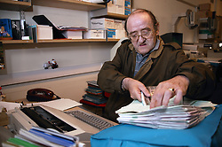 Man with disability working as microfilm technician in visual communications office,