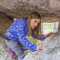 A girl plays in a small cave formed by large glacial erratics in the Stonehouse Forest in Barrington, New Hampshire.